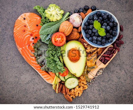 Heart shape of ketogenic low carbs diet concept. Ingredients for healthy foods selection on dark stone background. Balanced healthy ingredients of unsaturated fats for the heart and blood vessels.