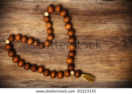 heart shape of rosary on wooden background