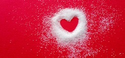 Heart shape on red cloth. Around the heart is white sugar, quite thick, and it fades away with a distance. The appearance of the sugar on the outside looks swaying.