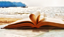 Heart shape paper book on the beach.valentine's day concept. symbol of love