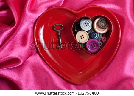Heart shape plate with buttons on rosy wave background