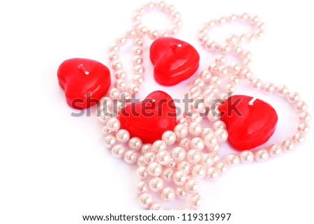 Heart shape red candles and necklace isolated on white background.