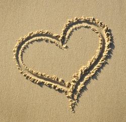 Heart shape symbol drawn on sandy beach