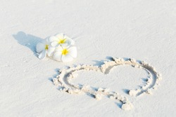 Heart shape symbol drawn on wet sand and decorated white plumeria flowers on sandy beach, Valentines Day background concept, tropical greeting card