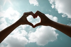 Heart shape with hand in sky