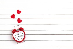 Heart-shaped alarm clock and hearts on white woooden background. Place for text. Top view. Time for love and greetings.