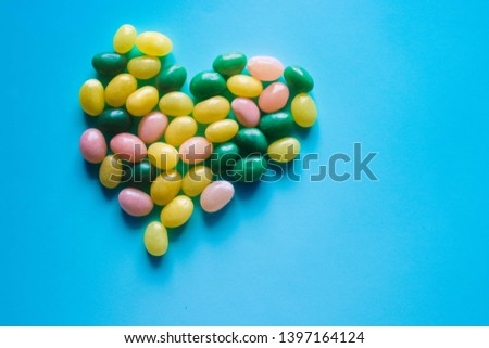 Heart shaped assorted multicolored jelly beans with blue background.