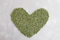 Heart shaped background or texture of green dry peas on a concrete background with place for text