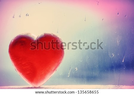 Heart-shaped bar of red translucent soap against window with raindrops background. - stock photo