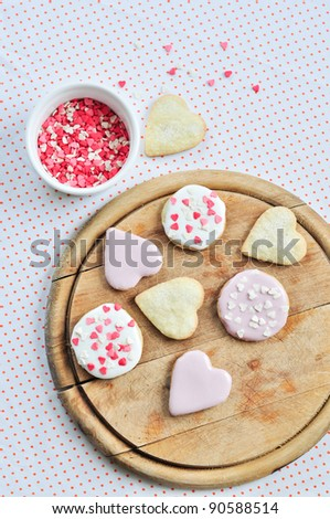Heart-shaped biscuits on a wooden board.