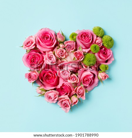 Heart shaped bouquet of beautiful fresh pink rose flowers on pastel blue background. Minimal Valentines Day, Easter, wedding or Mother's day concept. Creative spring or summer floral layout. Flat lay.