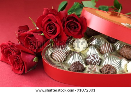 Heart shaped box filled with a variety of candies and long stem roses against a red background. Selective focus with shallow depth of field. - stock photo