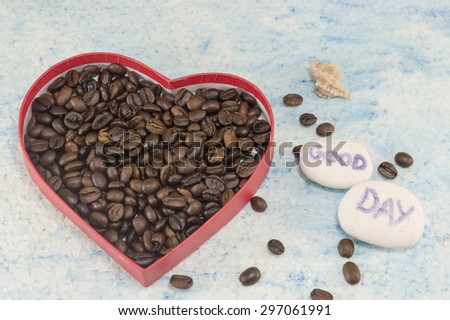 Heart shaped box filled with fried coffee beans on blue background with a \