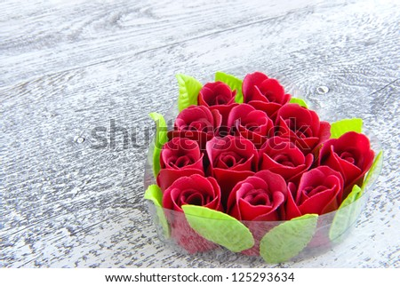 Heart-shaped box with red roses on wooden background
