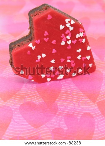 Heart shaped brownie with red icing and white and pink sprinkles on a pink placemat.