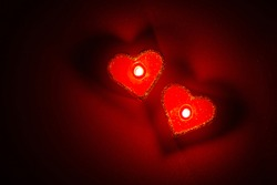 Heart shaped burning candles in dark red surrounding. Top view, isolated, close up.