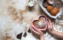 Heart shaped cake in pink baking dish. Muffins with chocolate, cream and chocolate. Breakfast for Valentine's Day. Female hands holding a cake. Cooking with love concept. Light background, top view