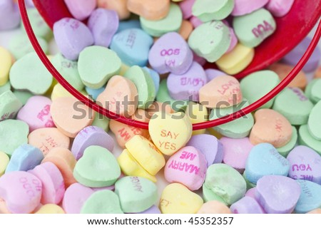 Heart shaped candy spilling from a red bucket. Shallow DOF with focus on center hearts that read Say Yes and Marry Me
