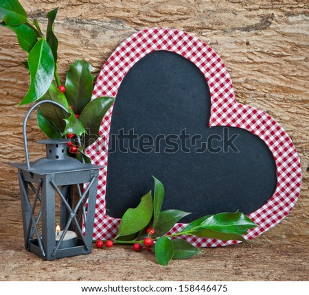 Heart-shaped chalkboard with a little lantern and holly branches