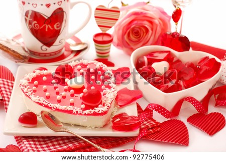 heart shaped cheese cake with jelly  on the table with valentine`s decoration