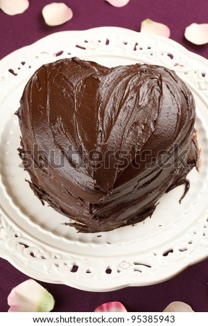 heart shaped chocolate cake in a traditional dish over a purple table cloth decorated with rose petals