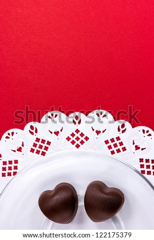 Heart shaped chocolate candy on glass saucer