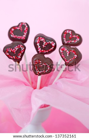 Heart shaped chocolate dipped cakepops with sprinkles on a pink background