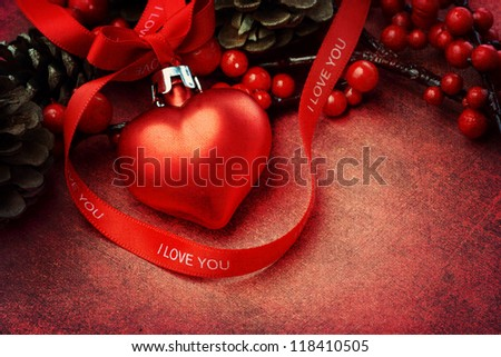 Heart shaped Christmas ornament with red 'I love you' ribbon on textured background