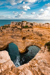 Heart-shaped cliffs on the shore of Atlantic ocean in Algarve, Portugal. Selective focus. Beautiful summer landscape.