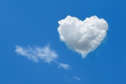 Heart shaped cloud on bright blue sky and white clouds.
