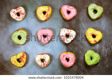 Heart shaped colored donuts on textured background #1025478004
