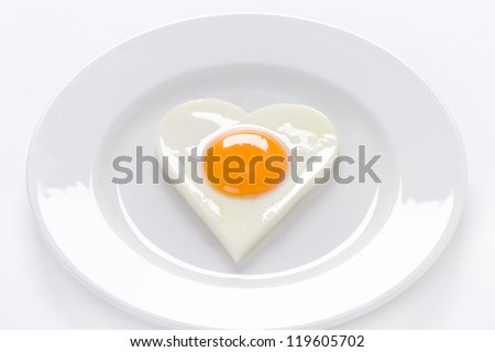 heart shaped cooked egg on a white plate - stock photo