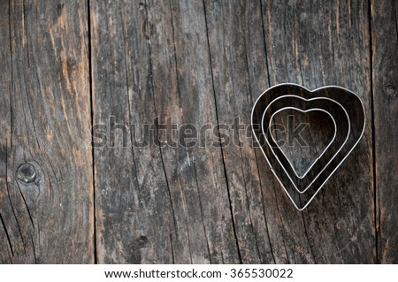 Heart shaped cookie cutter on a wooden background #365530022