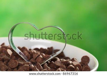 Heart-shaped cookie cutter on chocolate chips (Selective Focus, Focus on the front of the cookie cutter)