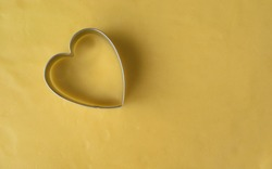 Heart shaped cookie cutter on cookies dough  background.