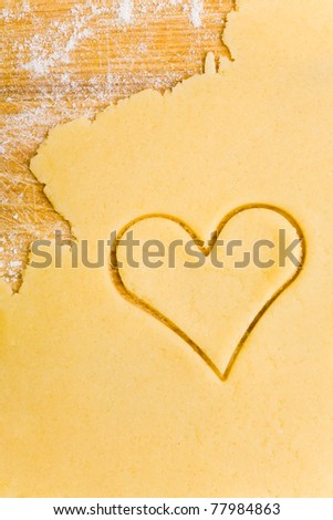 Heart shaped cookie cutter on raw cookie dough