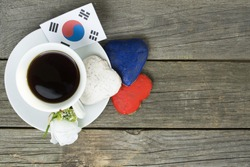 Heart shaped cookies color red, blue, white. Cup of coffee (tea), South Korea Flag decoration on old wooden table. Patriotic Breakfast Concept - information holidays, dates and events