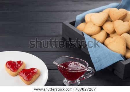 Heart shaped cookies decorated for Valentine's Day. Free space for text. Box with heart shaped cookies. Two heart shaped cookies with jam on a black wooden table. Like postcard #789827287