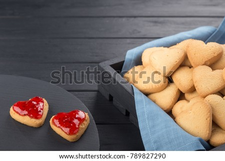 Heart shaped cookies decorated for Valentine's Day. Free space for text. Box with heart shaped cookies. Two heart shaped cookies with jam on a black wooden table. Like postcard #789827290