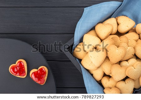 Heart shaped cookies decorated for Valentine's Day. Free space for text. Box with heart shaped cookies. Two heart shaped cookies with jam on a black wooden table. Like postcard #789827293