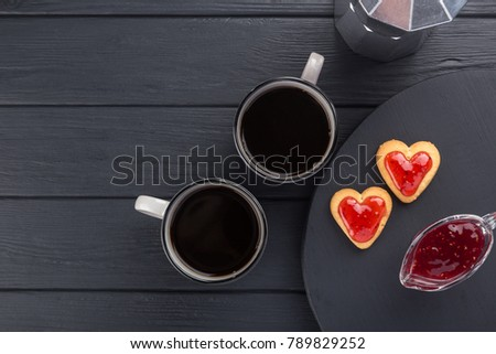 Heart shaped cookies decorated for Valentine's Day. Free space for text. Box with heart shaped cookies with coffee, coffee pot, jam on a black wooden table. Two heart shaped cookies with jam.  #789829252