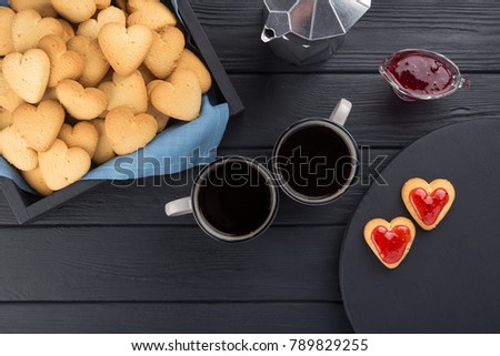 Heart shaped cookies decorated for Valentine's Day. Free space for text. Box with heart shaped cookies with coffee, coffee pot, jam on a black wooden table. Two heart shaped cookies with jam.  #789829255