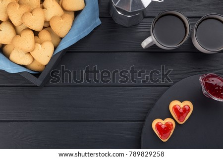 Heart shaped cookies decorated for Valentine's Day. Free space for text. Box with heart shaped cookies with coffee, coffee pot, jam on a black wooden table. Two heart shaped cookies with jam.  #789829258