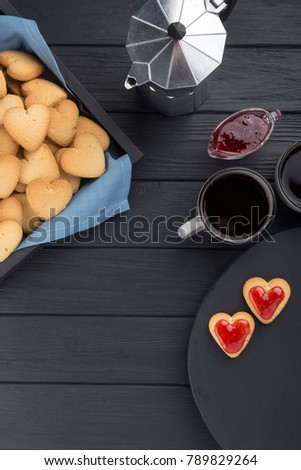 Heart shaped cookies decorated for Valentine's Day. Free space for text. Box with heart shaped cookies with coffee, coffee pot, jam on a black wooden table. Two heart shaped cookies with jam.  #789829264