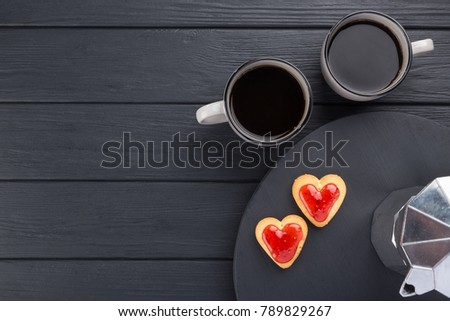 Heart shaped cookies decorated for Valentine's Day. Free space for text. Box with heart shaped cookies with coffee, coffee pot, jam on a black wooden table. Two heart shaped cookies with jam.  #789829267