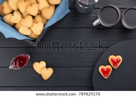Heart shaped cookies decorated for Valentine's Day. Free space for text. Box with heart shaped cookies with coffee, coffee pot, jam on a black wooden table. Two heart shaped cookies with jam.  #789829270