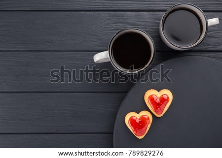 Heart shaped cookies decorated for Valentine's Day. Free space for text. Box with heart shaped cookies with coffee, coffee pot, jam on a black wooden table. Two heart shaped cookies with jam.  #789829276