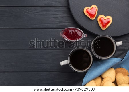 Heart shaped cookies decorated for Valentine's Day. Free space for text. Box with heart shaped cookies with coffee, coffee pot, jam on a black wooden table. Two heart shaped cookies with jam.  #789829309