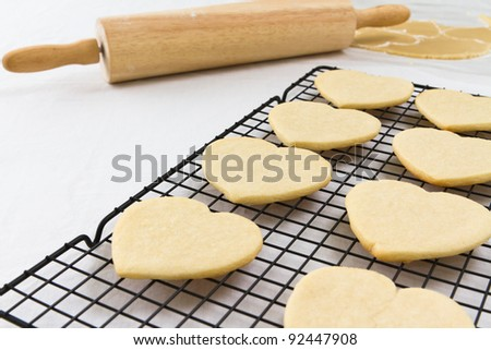 Heart shaped cookies on a cooling rack with a rolling pin and dough in the background.