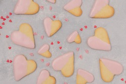 Heart-shaped cookies with pink chocolate glaze for Valentine's Day on the gray background. Recipe step by step. Valentine's Day food background. Top view
